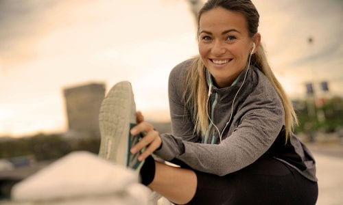 Young, single, athletic woman stretching before a run: health insurance comparison