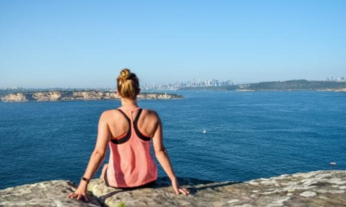 Young female hiker looks out over Sydney from the Royal National Park in NSW