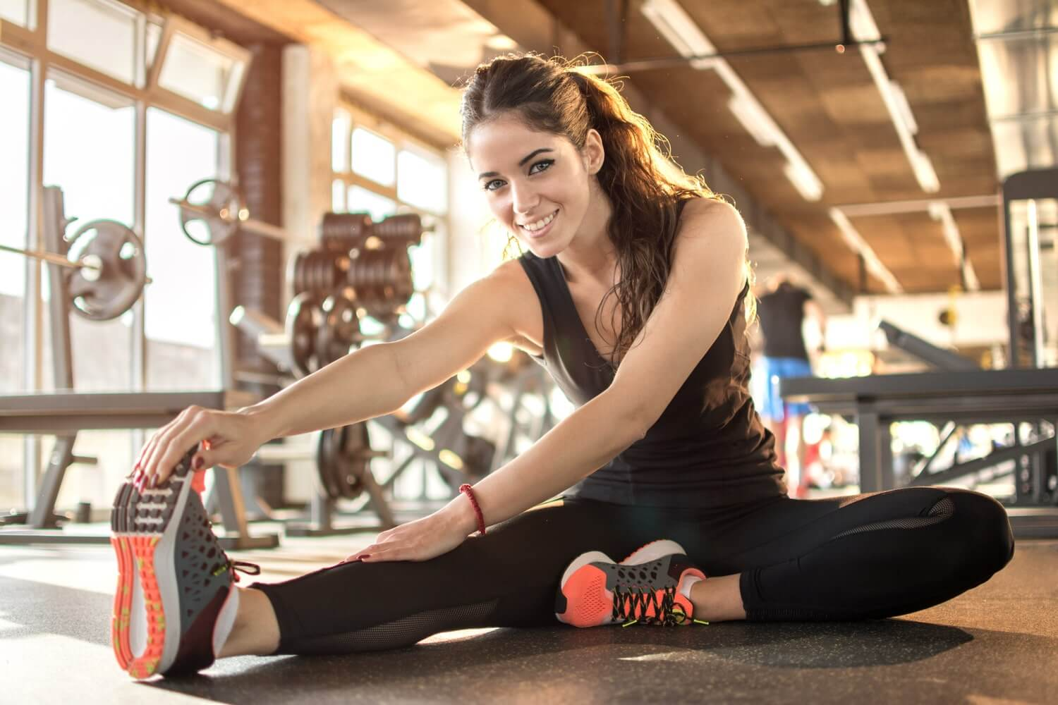Young Australian woman stretches in the gym