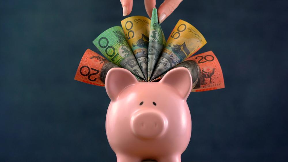Pink piggy bank money concept on dark blue background, stuffed with Australian money