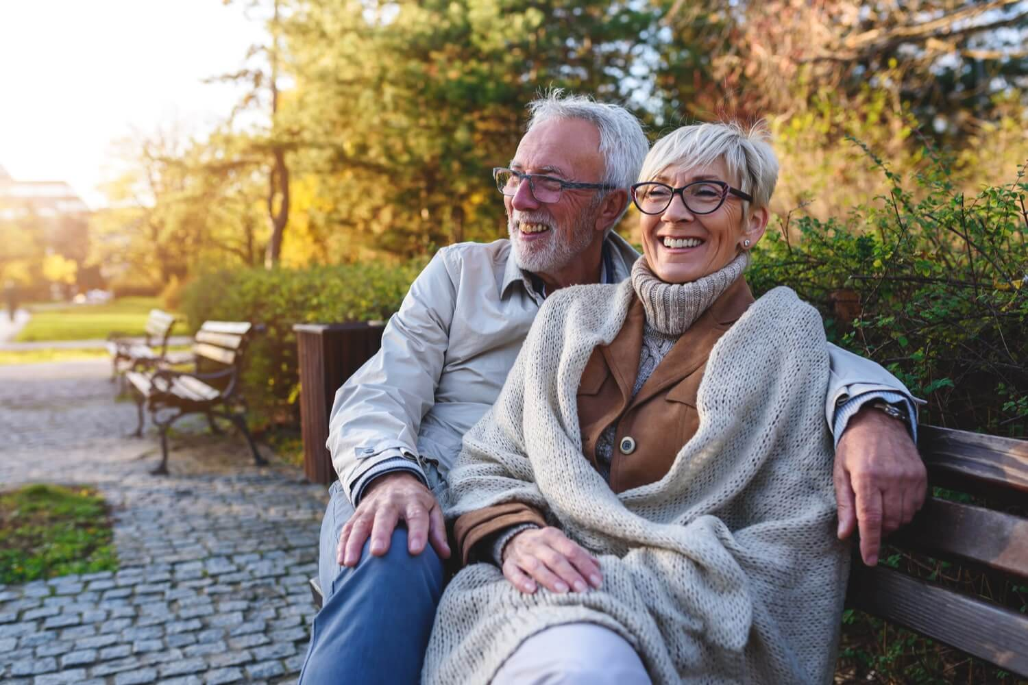Relaxed senior Australian couple sit on a bench