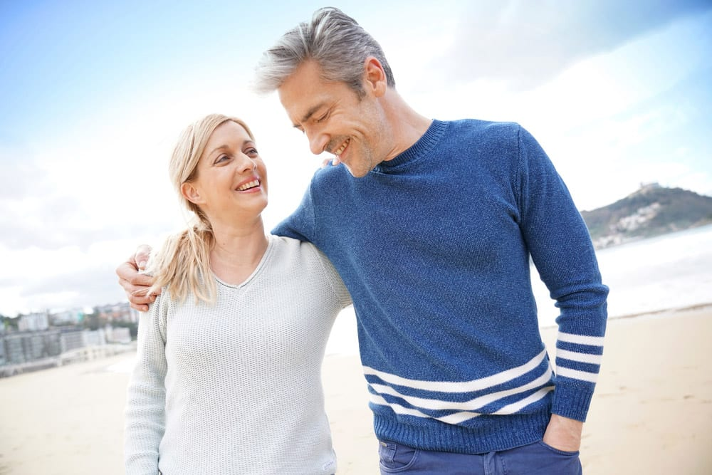 Mature Australian couple with life insurance walk across a beach
