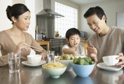Family having dinner around a table | Life Insurance Comparison