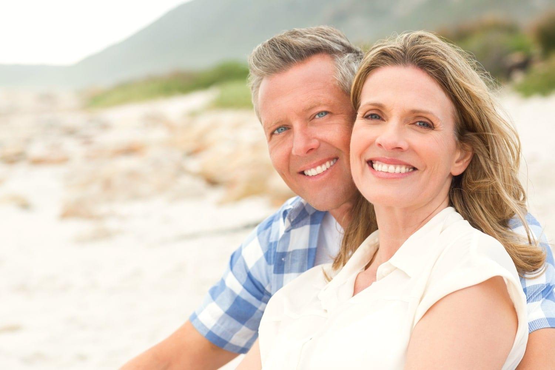 Australian couple in mid-40s sit on the beach